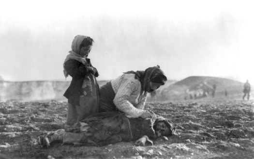 An Armenian woman kneeling beside a dead child in field within sight of help and safety at Aleppo, an Ottoman city.