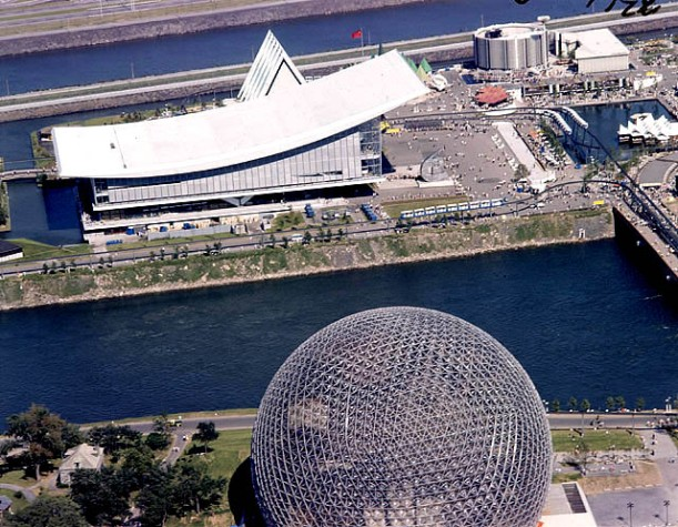 The Soviet pavilion with its sloping roof and faceless exterior sits across the water from the US geodesic dome.